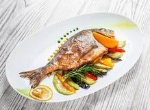 Grillad doradofisk med bakade grönsaker och rosmarin på plattan på träbakgrundsslut upp arkivfoto