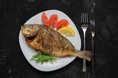 Grillad doradofisk på den vita maträtten på den svarta tabellen arkivfoto