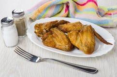 Grillad fega vingar i maträtt, salt, peppar, servett och gaffel Royaltyfria Foton