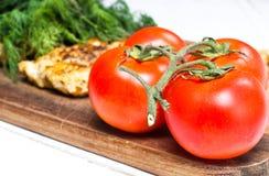 Grillad filé för fega bröst med nya tomater Arkivbild