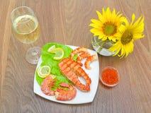 Grillad fisk med citronen, den röda kaviaren och räka, ett exponeringsglas av vin Royaltyfri Bild
