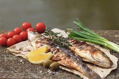 Grillad fisk som tjänas som på ett papper Arkivbilder