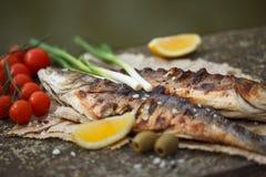 Grillad fisk som tjänas som på ett papper Arkivfoton