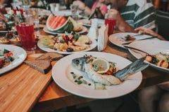 Grillad fiskfilé med BBQ-grönsaker och citroner Fotografering för Bildbyråer