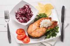 Grillad forell med grönsaker och ris på en trätabell Royaltyfri Fotografi