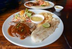 Grillad grisköttbiff och grillad fiskbiff Royaltyfri Fotografi