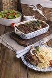 Grillad grisköttstöd och spaggeti Kött med kryddor och örter i disk på träbakgrund Äta lunch grillfesten med sallad och sås arkivfoto