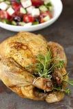 Grillad höna med örtar och grekisk sallad Arkivfoto