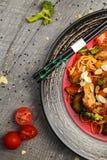 Grillad höna på en svart platta som lokaliseras bredvid grönsakerna, de röda pepparen och pinnarna Royaltyfri Fotografi