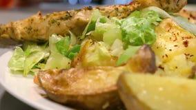 Grillad höna, potatisar och sallad på en platta i slut upp, kamerapanna stock video
