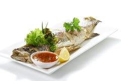 Grillad hel jätte- havsabborrefisk Pra-Kra-Pong med röda Chili Garlic Seafood Sauce och ett stycke av citronen på vitt porslin arkivfoton