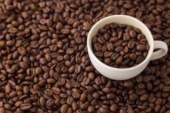 Grillad kaffebönor och kopp Arkivbild