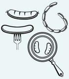 Grillad korv på gaffel och på stekpannan Arkivbild
