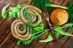 Grillad korvar, havrebulle och gaffellögn på en träyttersida med gräsplaner: grönsallat, dill, lök och persilja Picknick - grillf royaltyfri bild