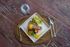 Grillad laxbiff tjänade som med pasta och grönsaker i ett litet Royaltyfria Bilder