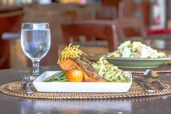 Grillad laxbiff tjänade som med pasta och grönsaker i ett litet Fotografering för Bildbyråer