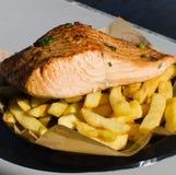Grillad laxfisk med chiper på en svart plast- platta fotografering för bildbyråer