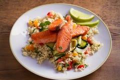 Grillad laxfisk med den tomatcouscous, zucchinin och limefrukt på den vita plattan royaltyfri bild