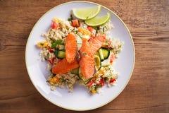 Grillad laxfisk med den tomatcouscous, zucchinin och limefrukt på den vita plattan Fotografering för Bildbyråer