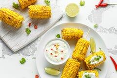 Grillad majs med den vit mexikansk sås, chili och limefrukt Sund sommarmat fotografering för bildbyråer