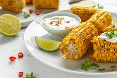 Grillad majs med den vit mexikansk sås, chili och limefrukt Sund sommarmat arkivfoto