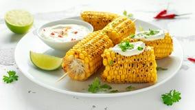 Grillad majs med den vit mexikansk sås, chili och limefrukt Sund sommarmat arkivfoton