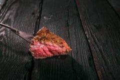 grillad meat spetsa ett stycke av biff på en gaffel Royaltyfria Bilder