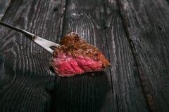 grillad meat spetsa ett stycke av biff på en gaffel Arkivfoton