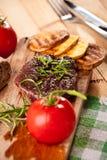 Grillad nötköttbiff, bakade potatisar och grönsak på träbröd Royaltyfria Foton