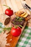 Grillad nötköttbiff, bakade potatisar och grönsak på träbröd Arkivbild
