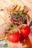Grillad nötköttbiff, bakade potatisar och grönsak på träbröd Royaltyfria Bilder