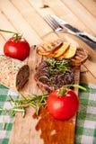 Grillad nötköttbiff, bakade potatisar och grönsak på träbröd Royaltyfri Foto