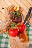Grillad nötköttbiff, bakade potatisar och grönsak på träbröd Arkivfoto