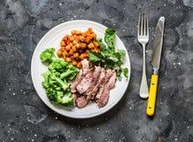 Grillad nötköttbiff, kryddiga kokta kikärtar, broccoli - läcker sund lunch på en mörk bakgrund, bästa sikt royaltyfri foto