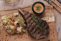 Grillad nötköttbiff på benstriploin med ris och grönsaker royaltyfri bild