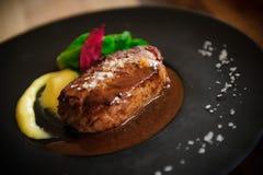 Grillad nötköttfläskkarré med sås och grönsallat på det svarta uppläggningsfatet Arkivfoton