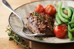 Grillad nötköttsteak med timjan och grönsaker Arkivfoto