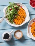 Grillad sötpotatis- och arugulasallad - läckert vegetariskt mellanmål på blå bakgrund arkivbilder