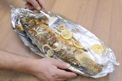 Grillad skaldjur-karp fisk i folie Kocken fick precis fisken ut ur ugns- och portionmaträtten med citroner arkivfoto