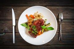 Grillad Striploin biff med grönsaker på plattan royaltyfri bild