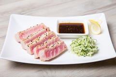 Grillad tonfisk med sesamfrö och gurkasallad på en vit platta royaltyfri bild