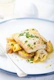 Grillad torsk, codfish med bakade potatisar och kronärtskockor Arkivfoto