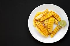 Grillade ananaskilar med limefrukt på en vit platta över svart bakgrund, närbild Sommarmat Bästa sikt som är över huvudet, från ö arkivfoton