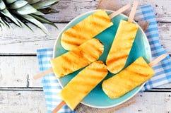 Grillade ananaskilar på den blåttplattan och torkduken mot vitt trä Arkivbild