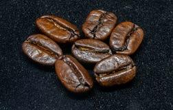 Grillade bönor av kaffe på svart bakgrund Royaltyfri Bild