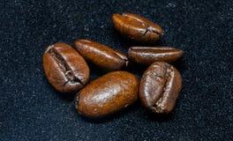 Grillade bönor av kaffe på svart bakgrund Royaltyfria Foton