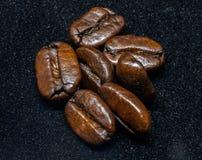 Grillade bönor av kaffe på svart bakgrund Arkivfoto