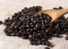 Grillade bönor för svart kaffe och träsked i kaffe fotografering för bildbyråer