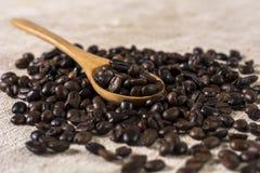 Grillade bönor för svart kaffe och träsked i kaffe royaltyfri foto