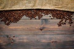Grillade bönor nära kanfas på mörk träcopyspace för bästa sikt för tabell klart bruk för bakgrundskaffe Royaltyfri Foto